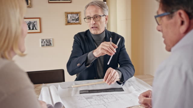 architect presenting plan details to senior couple in their home - weight scale stock videos and b-roll footage