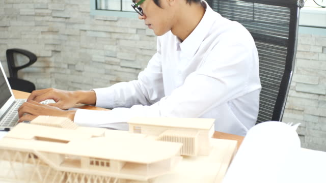 LD Architect putting a roof on his architectural model