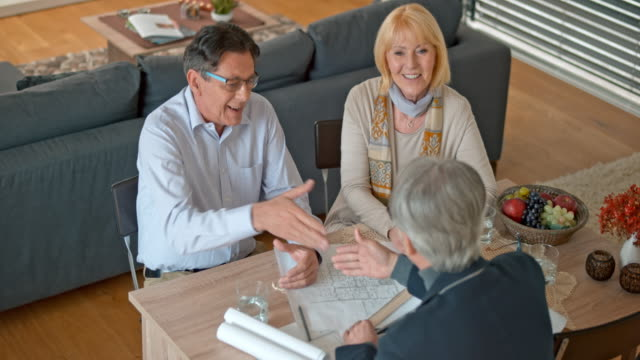 Architect shaking hands with a senior couple in their home