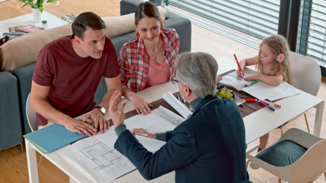 Architect shaking hands with his clients at a meeting in their home
