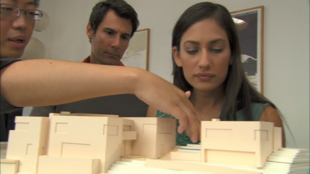 CU, Architect showing architectural model to colleagues