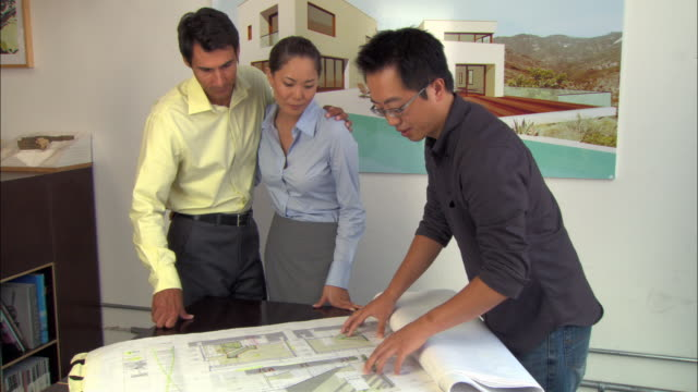 ms, architect showing blueprint to couple - poster layout stock videos & royalty-free footage