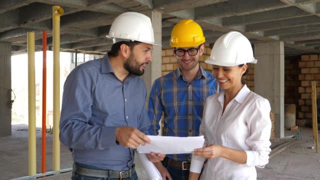 Architekt, zeigt den Grundriss der Wohnung zu einem Paar, ging zu die Baustelle, auf der Suche sehr glücklich und lächelnd zu sehen