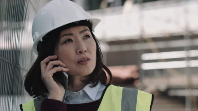 architect speaking on phone on construction site - 建設作業員点の映像素材/bロール