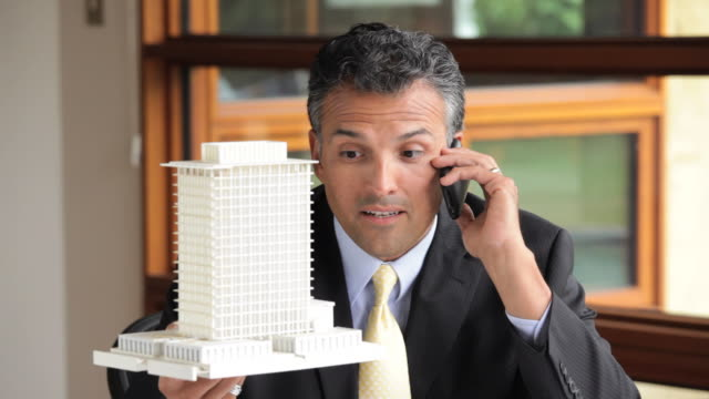 MS Architect Talking on Cell Phone, Looking at Model Building in Office / Richmond, Virginia, USA