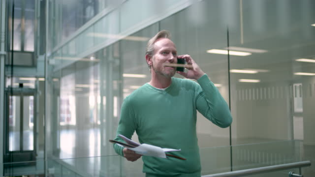 WS MS of architect talking on cell phone on office balcony
