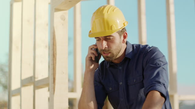 architect talking on the phone at construction site - manual worker stock videos & royalty-free footage