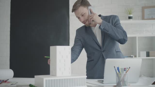 4 k : architekt spricht am telefon im seinem büro. - lageplan stock-videos und b-roll-filmmaterial
