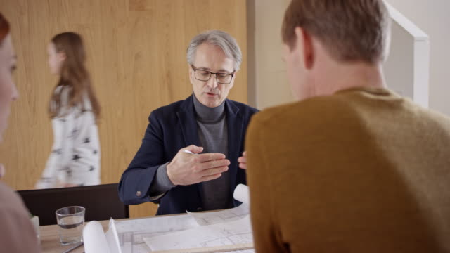 Architect talking to his clients in their house