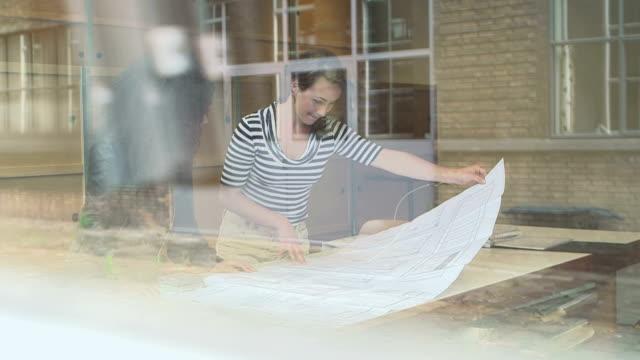 vídeos de stock e filmes b-roll de architect team looking at blue print drawing in office - arquiteta