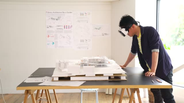 architect using a vr headset to explore a 3d architectural model - architetto video stock e b–roll