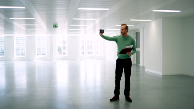 WS of architect using cell phone in empty office