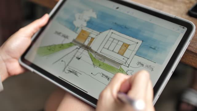 vídeos de stock e filmes b-roll de architect using digital tablet comment detail on home sketch with digital tablet - arquiteta