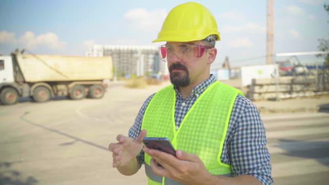 建設現場で携帯電話を使用する建築家 - ダンプカー点の映像素材/bロール