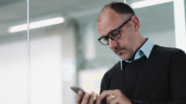 architect using phone in contemporary office - balding stock videos & royalty-free footage