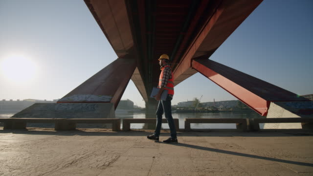 architect with a laptop walks under a bridge on a construction site - bridge built structure stock videos & royalty-free footage