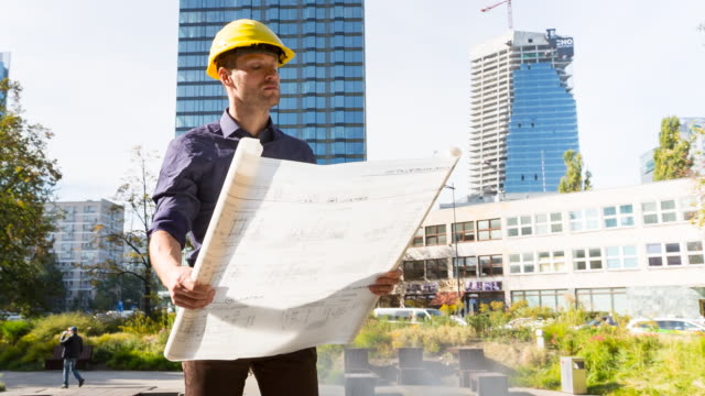 MS PAN architect with building plans in front of high rise construction