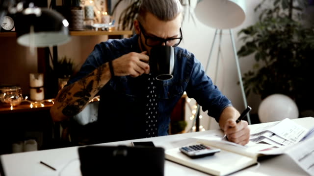 Architect working at laptop in office and drinking coffee