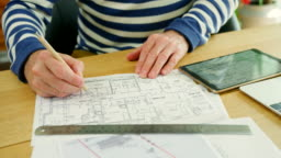 Architect Working On Construction Design Blueprints At His Desk