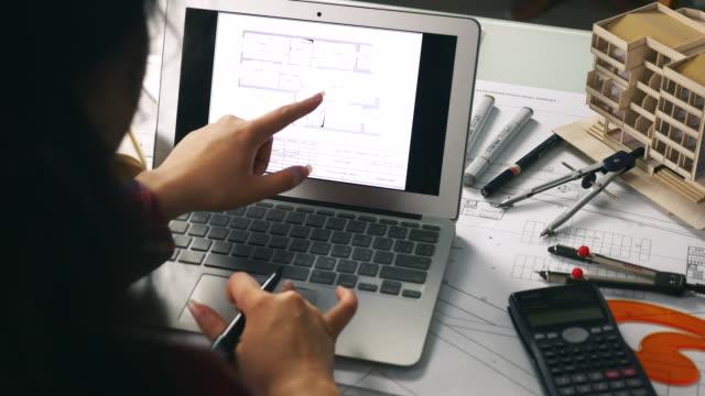 vídeos de stock e filmes b-roll de architect working on laptop in office - arquiteta