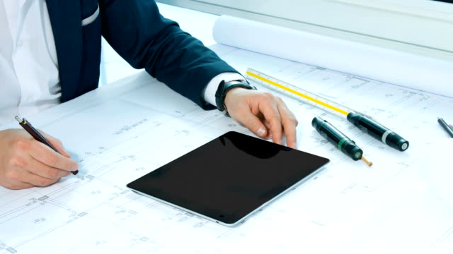 Architect working on table with digital tablet