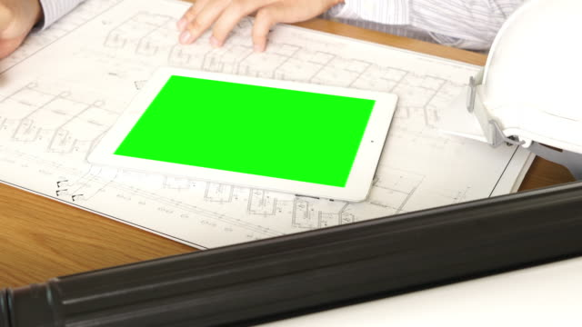 Architect working on table with green screen