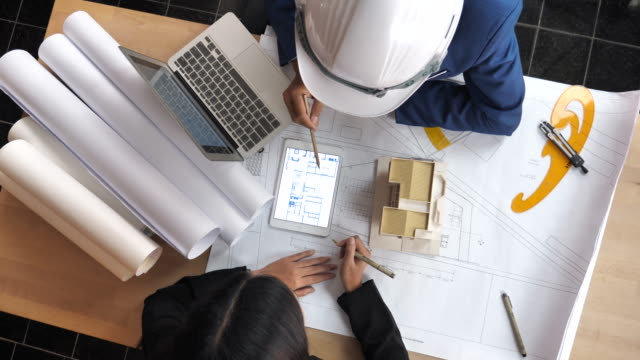 Architects and clients defining the design details with Blueprint and Architectural Model, Directly Above