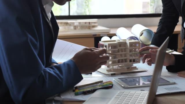 vidéos et rushes de architectes et ingénieurs réunion ou discuter sur le modèle de l'architecte au bureau - architecte