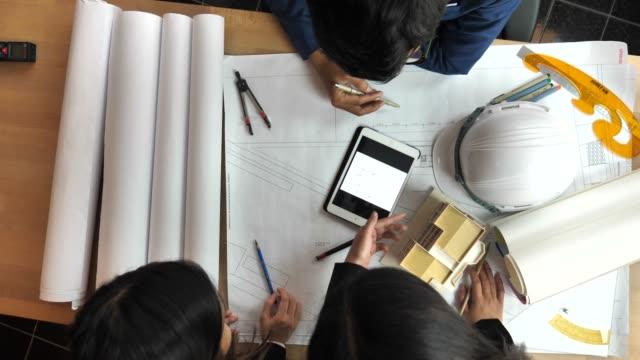 architekten und ingenieure treffen oder diskutieren über baupläne im büro - baustelle stock-videos und b-roll-filmmaterial