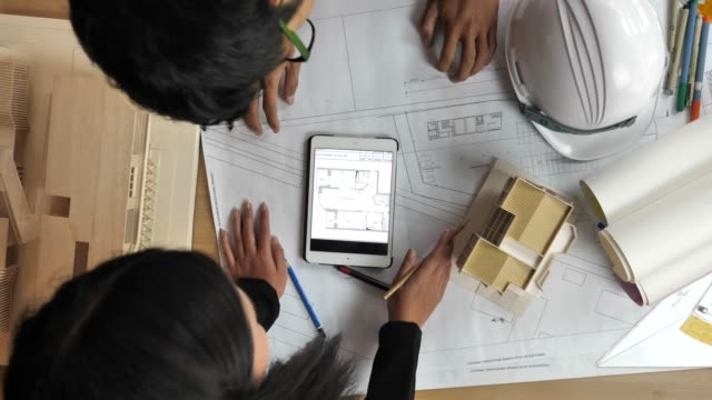 architects and engineers meeting or discussing on blueprints in the office - caposquadra video stock e b–roll