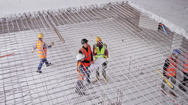 ld architects and foreman talking on the ground floor of the building under construction - construction site stock videos & royalty-free footage