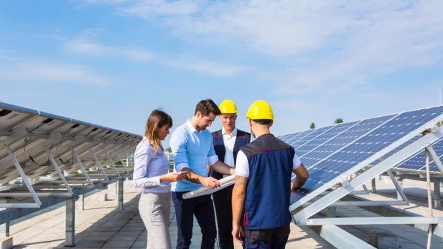 MS architects and workers discussing solar panels on rooftop