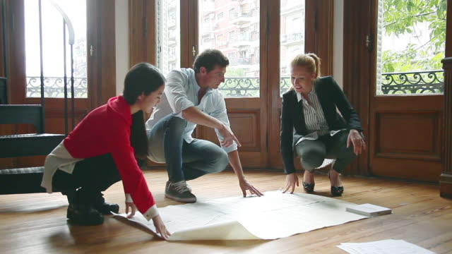Architects discussing blueprints together