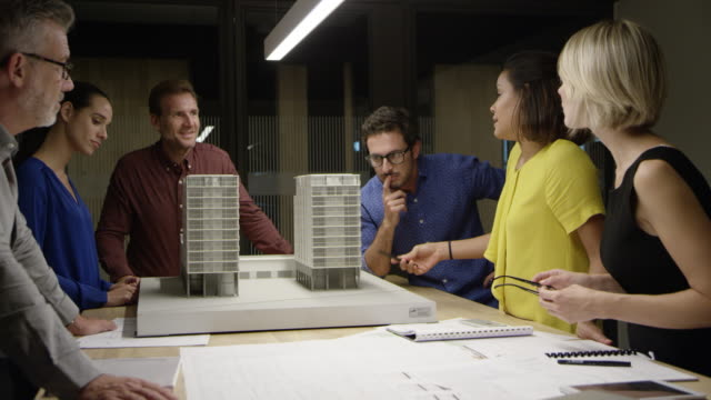 architects discussing over building model at table - architectural model stock videos & royalty-free footage