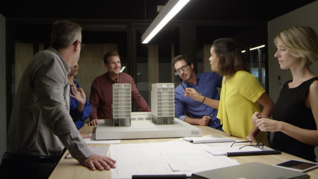 architects discussing over building model at table - architetto video stock e b–roll