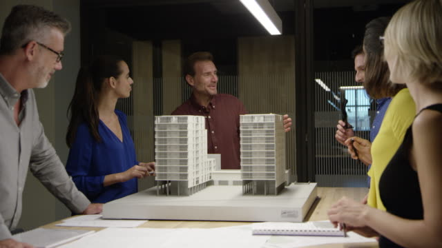 architects discussing over building model at table - architectural model stock videos and b-roll footage