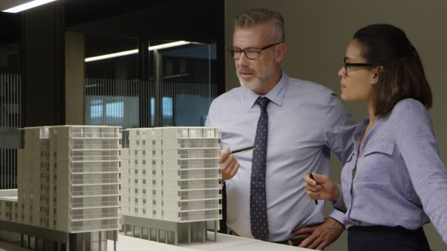 architects examining model building in office - architetto video stock e b–roll