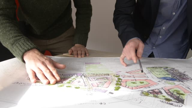 Architects looking at design drawings close up.