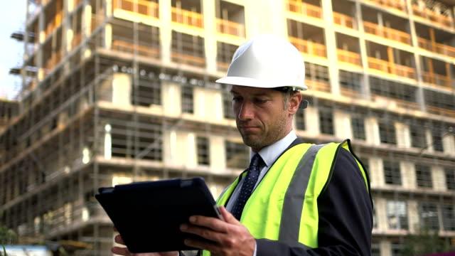 vídeos y material grabado en eventos de stock de architects on construction site with digital tablet - un solo hombre maduro