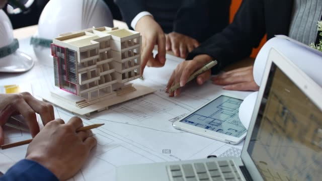 vídeos de stock e filmes b-roll de architects team brainstorming the design solutions with architect model - obra