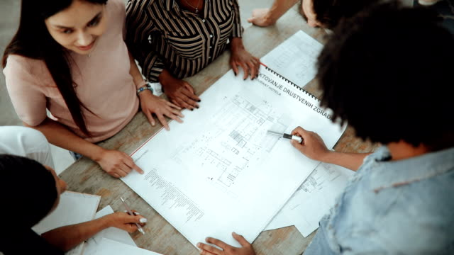 architects team defining the design details with blueprint - architect stock videos & royalty-free footage
