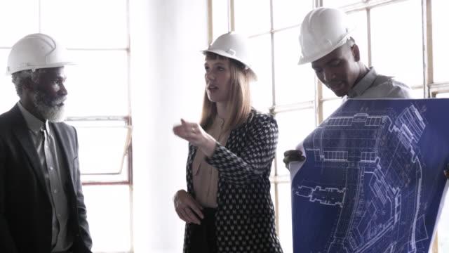 vídeos de stock, filmes e b-roll de architects with hard hats look at blueprints, close up - capacete de trabalho