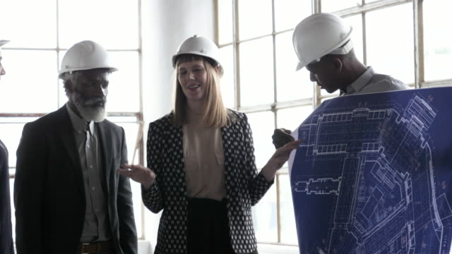 stockvideo's en b-roll-footage met architects with hardhats look over blueprints, rack focus - 30 34 jaar