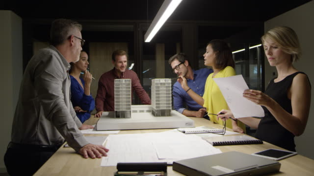 architects working on project at table in office - architetto video stock e b–roll