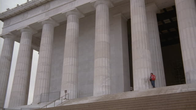 pan architectural detail, entrance, stairs, and columns of the lincoln memorial, with pedestrians / washington, d.c., united states - fries säulengebälk stock-videos und b-roll-filmmaterial
