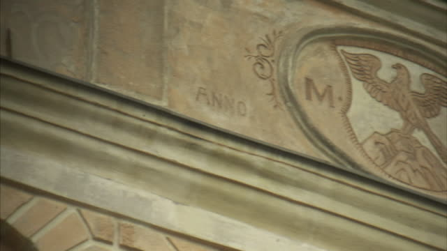 Architectural ledge detail on building PAN to engraved Town Crest falcon w/ wings spread perched on hilltop MF letters each side dated MCLXXI State...