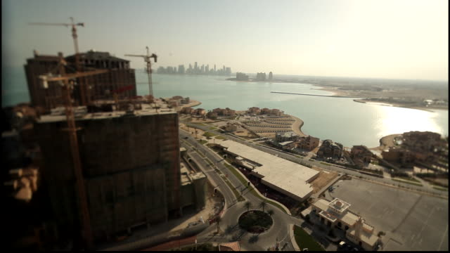 tilt-shift miniature effect. view of a building under construction against the doha skyline using a tilt-shift lens. - gulf countries stock videos & royalty-free footage