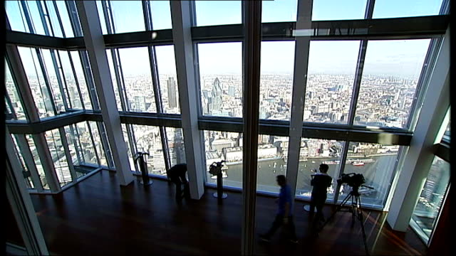 'the shard' and views from inside england london london bridge ext low angle view 'the shard' skyscraper against clear blue sky tilt down road works... - shard london bridge stock videos & royalty-free footage
