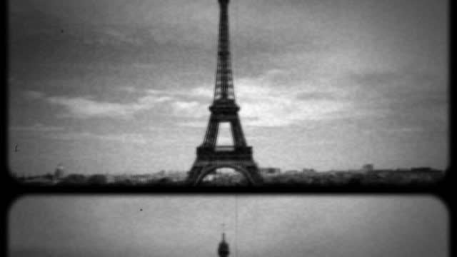 archival black and white film footage of the eiffel tower set against a cloudy sky. - newsreel stock videos & royalty-free footage