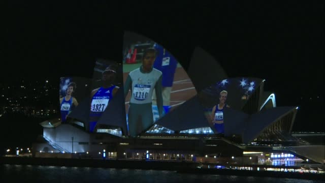 stockvideo's en b-roll-footage met archival footage of australian athlete cathy freeman's 2000 olympic race recorded on a dna data storage is projected onto sydney's iconic opera house... - clean